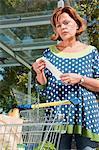 Senior woman holding supermarket receipt