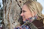 Woman hugging tree trunk, smiling, Bavaria, Germany