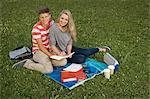 Portrait of teenage couple doing homework in park, smiling