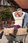 Daughter in wheelbarrow hugging father