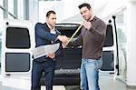 Customer and salesman checking van measurements in car dealership
