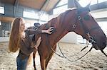 Female horseback rider grooming horse in indoor paddock