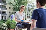 Gay man looking at partner while having coffee at porch