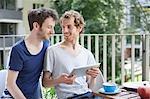 Young gay couple using digital tablet at porch