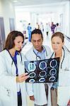 Doctors examining x-rays in hospital hallway