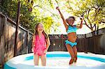 Two girls jumping in garden paddling pool