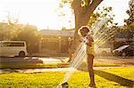 Girl standing in garden sprinkler