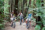 Three mid adult women mountain bikers using smartphones  in forest