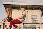 Young couple laughing on lifeguard hut, Santa Monica, California, USA