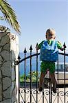 Boy climbing on gate, Sicily, Italy