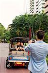Man taking photo of friends in auto rickshaw