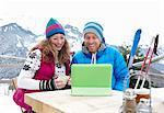 Ski couple using digital tablet.
