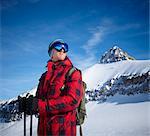 A man in front of snowy, mountain peak. Blue sky.