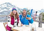 Portrait of seated couple in ski wear.