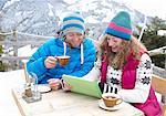 Couple using digital tablet in winter landscape.
