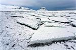 Winter view over slabs of broken lake ice covered in snow towards Kirkjufell (Church Mountain), near Grundarfjordur, Snaefellsnes Peninsula, Iceland, Polar Regions