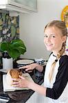 Girl cutting bread in kitchen