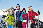 Smiling family holding ski poles on mountain