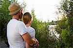 Romantic mid adult couple watching lakeside sunset