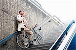 Mature businessman on subway steps drinking takeaway coffee