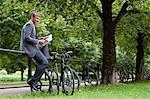 Mature businessman sitting on park railings reading newspaper