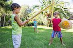 Three children in garden playing with toy swords