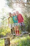 Three children standing on garden seat with arms around each other