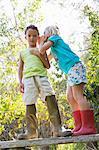 Girl whispering to boy whilst standing on garden bench