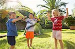 Three children in garden flexing muscles