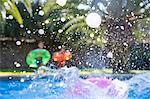 Three children making a splash in garden swimming pool