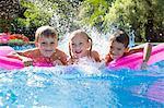 Portrait of three children splashing on inflatable mattress in garden swimming pool