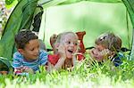 Three children lying chatting in garden tent