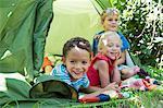 Portrait of three smiling children lying in garden tent
