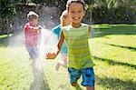 Three children chasing each other in garden with water sprinkler