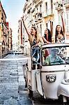 Three young women waving from open back seat of Italian taxi, Cagliari, Sardinia, Italy