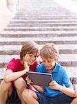 Brothers looking at digital tablet on village steps, Majorca, Spain