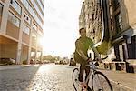 Male messenger cycling along city street