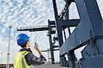 Worker using walkie-talkie under cargo crane