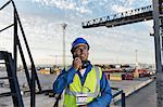 Worker using walkie-talkie on cargo crane