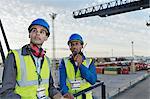 Workers standing on cargo crane