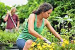 Woman wearing tank top and gloves gardening, man raking in background