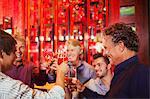 Five smiling men raising toast in bar
