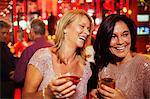 Two smiling mature women enjoying drinks in nightclub