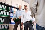 Three men office talking laughing working