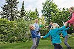 Parents and children dancing on garden lawn