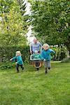 Father in garden pushing kids in wheelbarrow