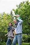 Parents mother father baby piggyback garden