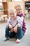 Portrait of two little sisters in kindergarten