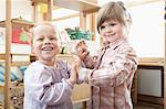 Two smiling little girls holding hands in kindergarten