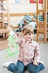 Portrait of smiling little girl holding paper christmas tree